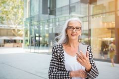 Stylish senior woman holding a mobile in a street Stock Photo