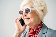 Stylish senior woman in jacket and sunglasses talking on smartphone,. Isolated on grey Royalty Free Stock Photo