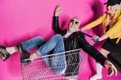 Stylish senior woman pushing shopping trolley with joyful senior man having fun. Smiling stylish senior women pushing shopping trolley with joyful senior men Royalty Free Stock Photo