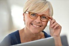 Stylish senior woman wearing eyeglasses and using tablet Stock Images