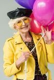 Stylish senior woman in yellow jacket with colorful balloons,. Isolated on grey stock image