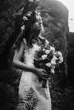 Stylish sensual bohemian bride in a fairytale with bouquet on background of rocks in mountains. Light stock images