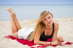 Stylish sexy girl in white jeans shorts. Resting on a  beach, enjoying the sun; freedom summertime concept. Royalty Free Stock Photography