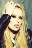 Stylish sexy woman. Portrait of one beautiful sensual sexy young serious passionate blonde woman touching head and long hair with hand in leather black jacket in stock image