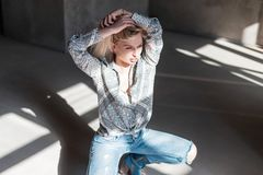 Stylish sexy young blond woman in a vintage summer shirt in fashionable blue ripped jeans in green cowboy boots posing. Sitting indoors with sunlight. Pretty stock photos