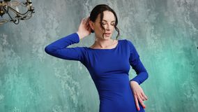 Stylish sexy young girl model stands in a long blue dress. In the Studio stock video