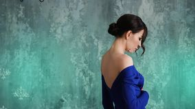 Stylish sexy young girl model stands in a long blue dress. In the Studio stock footage