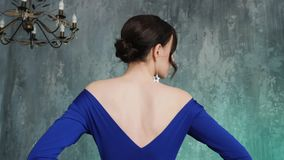 Stylish sexy young girl model stands in a long blue dress. In the Studio stock video footage