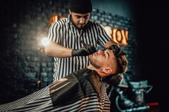 Old fashioned cutting in dark retro styled barbershop. Stylish shaving and caring in professional dark saloon where barber cutting beard of his favourite client
