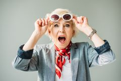 Stylish shocked senior lady in scarf and sunglasses,. Isolated on grey royalty free stock image