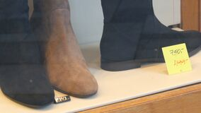 Stylish shoes made of suede leather on the window of a shoe store with price tags and discounts.  stock video