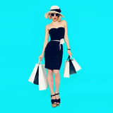 Stylish shopping lady with shopping bags on blue background.  Royalty Free Stock Photo
