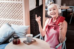 Stylish short-haired old lady in pink outfit showing rock gesture stock photography