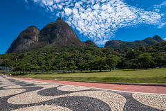 Stylish Sidewalk, Green Park, and Mountains. Famous Copacabana Style Mosaic Sidewalk and Beautiful Mountain Landscape With Pedra da Gavea in Rio de Janeiro Royalty Free Stock Photography