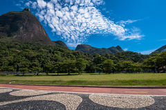 Stylish Sidewalk, Green Park, and Mountains. Famous Copacabana Style Mosaic Sidewalk and Beautiful Mountain Landscape With Pedra da Gavea in Rio de Janeiro Royalty Free Stock Images