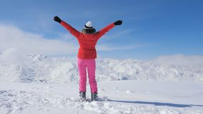 A Stylish Skier Woman On Peak Mountain, Raises Hands Up. Active skier woman on the snow covered mountain background, raises her hands, enjoying such an amazing stock images