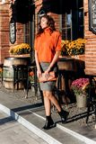 Stylish slim girl dressed in gray skirt, orange blouse holding orange little bag walks in the street on a sunny day royalty free stock photo