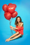 Stylish, smiling, beautiful woman with balloons over blue background Royalty Free Stock Images