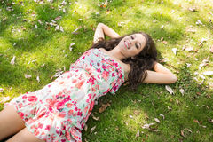 Stylish smiling brunette lying on the grass Stock Photos