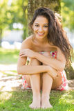 Stylish smiling brunette sitting under a tree Stock Photography