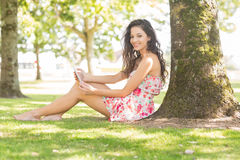 Stylish smiling brunette sitting under a tree using tablet Stock Images
