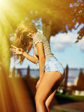 Stylish smiling girl in bright casual cloth in jeans shorts outdoors Royalty Free Stock Photo