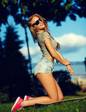 Stylish smiling girl in bright casual cloth in jeans shorts outdoors Stock Photography
