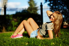 Stylish smiling girl in bright casual cloth in jeans shorts outdoors Stock Image
