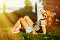 Stylish smiling girl in bright casual cloth in jeans shorts outdoors Stock Photos