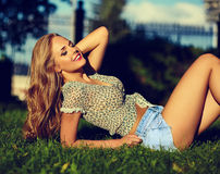 Stylish smiling girl in bright casual cloth in jeans shorts outdoors Stock Photo
