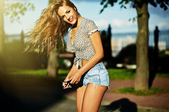 Stylish smiling girl in bright casual cloth in jeans shorts outdoors Royalty Free Stock Images