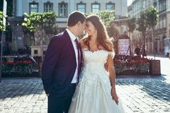 Stylish smiling just married are smiling and touching noses in the sunny street. Stylish smiling just married are smiling and touching noses in the sunny street Stock Image