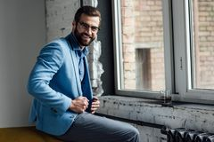 Stylish smiling man in eyeglasses and blue trendy suit sitting. At window Stock Photos