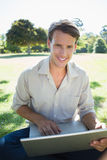 Stylish smiling man using his laptop in the park Stock Image