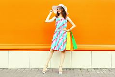 Stylish smiling woman with shopping bags wearing colorful striped dress, summer straw hat posing on orange wall royalty free stock photos