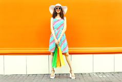Stylish smiling woman with shopping bags wearing colorful striped dress, summer straw hat posing on orange wall stock photography