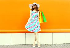 Stylish smiling woman with shopping bags wearing colorful striped dress, summer straw hat posing on orange wall royalty free stock images