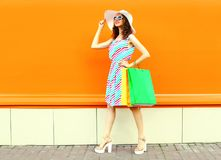 Stylish smiling woman with shopping bags wearing colorful striped dress, summer straw hat walking over orange wall royalty free stock photo