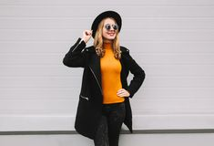 Stylish smiling young woman posing in city. On gray wall background stock photos