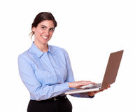 Stylish smiling young woman using a laptop Royalty Free Stock Photo