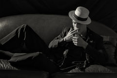 Stylish Smoker. Fashionable Young Man Lighting a Cigarette. Stylish smoker. Handsome young man wearing elegant suit with hat lying on the couch while lighting a royalty free stock photography