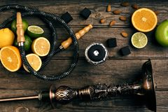 Stylish Smoking hookah and basket with lemon, lime and orange on. Wooden background. Top view. Flat lay. Copy space. Still life royalty free stock photos