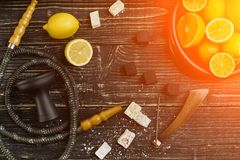 Stylish Smoking hookah and basket with lemon, lime and orange on. Wooden background. Top view. Flat lay. Copy space. Still life. Sun flare royalty free stock image