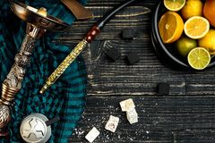 Stylish Smoking hookah and basket with lemon, lime and orange on. Wooden background. Top view. Flat lay. Copy space. Still life royalty free stock image