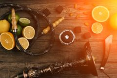 Stylish Smoking hookah and basket with lemon, lime and orange on. Wooden background. Top view. Flat lay. Copy space. Still life. Sun flare royalty free stock photo