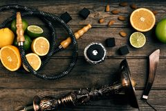 Stylish Smoking hookah and basket with lemon, lime and orange on. Wooden background. Top view. Flat lay. Copy space. Still life royalty free stock images