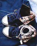 Stylish sneakers and gadgets. Stylish denim sneakers and gadgets Stock Image