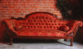 Stylish sofa. Red retro stylish sofa near wall from break Royalty Free Stock Photos