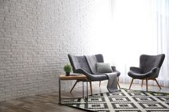 Stylish sofa and armchair near brick wall in modern room interior. Space for text. Stylish sofa and armchair near brick wall in modern living room interior stock images