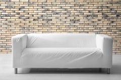 Stylish sofa near brick wall Stock Images